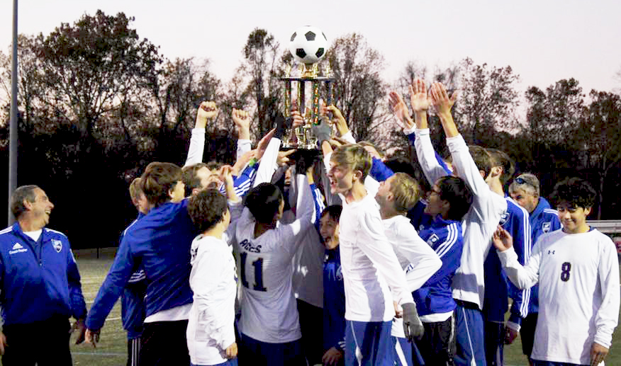 Boys Soccer Champions lifting the trophy